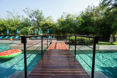 Wooden walkway across swimming pool in hotel Royalty Free Stock Images