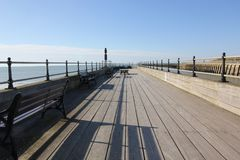Wooden walkway over the sea. A wooden walkway from the beach into the sea against a blue sky with railings and benches, sunshine and shadows Royalty Free Stock Image