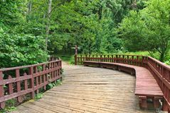 Wooden walkway with benches and fence in the forest royalty free stock image
