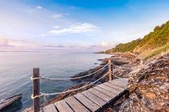 Wooden walkway bridge seashore with mountain landscape in sunrise Stock Photo