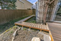 Wooden walkway inside the yard of a home viewed on a sunny day. The walkway is connected to a wooden deck with a reflective glass door leading inside the house royalty free stock photo