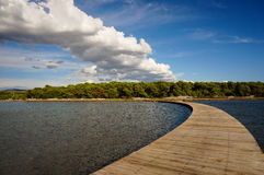 Wooden walkway leading into the horizon. clouds mirroring the pathway. Curved wooden boardwalk is connecting the mainland with an island clouds are mirroring the Stock Photo