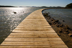 Wooden walkway leading into the  horizon. Curved wooden boardwalk is connecting the mainland with an island Royalty Free Stock Photography