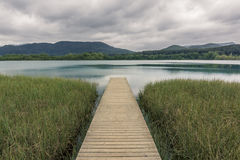 Wooden walkway leading to the lake. Vanishing point Stock Image