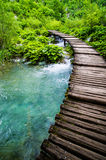 Wooden walkway over flowing river Stock Photography