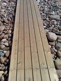 Wooden walkway over pebbles Royalty Free Stock Images