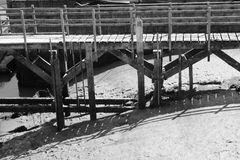 Wooden walkway over the river at low tide. A black and white shot of a wooden walkway to the river uncovered at low tide.  The sun has thrown reflections and Stock Photos