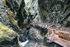 Wooden walkway over the rough river. Austria, Kaprun Stock Photos