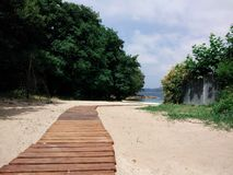 Wooden walkway over the sand dunes to the paradisiacal beach between green trees stock photos