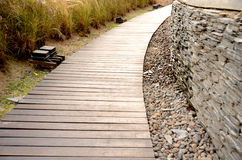Wooden walkway and stone wall Royalty Free Stock Photo