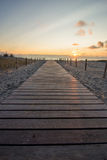 Wooden walkway to beach at sunset Royalty Free Stock Image