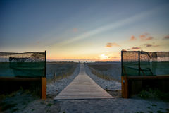 Wooden walkway to beach at sunset Royalty Free Stock Photo