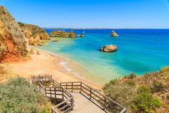 Wooden walkway to famous Praia Dona Ana beach. With turquoise sea water and cliffs, Portugal Royalty Free Stock Image