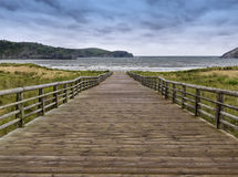 Wooden walkway to the sea. With a cloudy sky Stock Photo