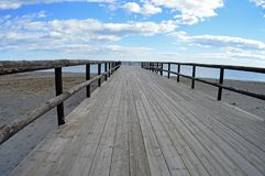 Wooden walkway to the sea. A wooden planked walkway with a blue sky and clouds, suitable for a background or backdrop Royalty Free Stock Image