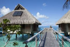 Free Wooden Walkways Over The Water Of The Blue Tropical Sea To Authentic Traditional Polynesian Thatched Roof Houses With Eco-friendly Stock Images - 163724854