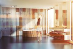 Wooden wall bathroom, tub and sink, woman. Woman standing in modern bathroom interior with gray and wooden walls, wooden tub, double sink with two narrow mirrors royalty free stock image