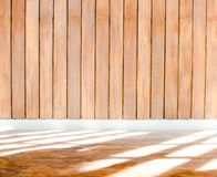 Wooden wall with cement trim and light shade on stone floor Stock Image