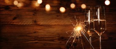 Wooden wall with champagne and sparkler. Rustic wooden wall with champagne and sparkler for a festive occasion Royalty Free Stock Images
