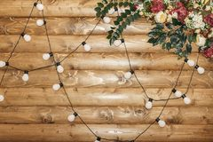 Wooden wall decorated by electric garland and flowers. Decoration for wedding or Reception. Copy space stock photo