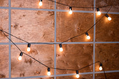Wooden wall decorated by electric lamps. Decorative antique edison style. Stock Image