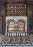 Wooden wall decorated with painted floral patterns, double embedded arched niche and marble floor decorated with geometric pattern stock photography