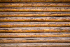 Wooden wall. Wall from a large number of old brown logs Stock Photography