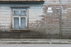 Wooden wall of the old house with a window and a sign as backgro Stock Image