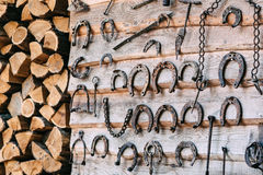 Wooden wall with old rusty horseshoes  and firewood. Set of old rusty horseshoes and firewood on a wooden background. A concept on excavation, archeology, the Royalty Free Stock Image