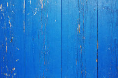 Wooden wall with peeling blue paint. Surface of vertical wooden planks covered with weathered blue paint royalty free stock photos