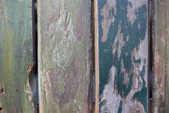 Wooden wall with peeling colorful paint. Surface of vertical wooden planks covered with weathered colorful paint stock photo