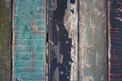 Wooden wall with peeling colorful paint. Surface of vertical wooden planks covered with weathered colorful paint royalty free stock photography