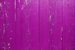 Wooden wall with peeling purple paint. Surface of vertical wooden planks covered with weathered purple paint royalty free stock photo