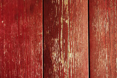 Wooden wall with peeling red paint. Surface of vertical wooden planks covered with weathered red paint royalty free stock image