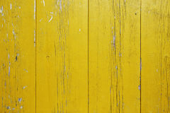 Wooden wall with peeling yellow paint. Surface of vertical wooden planks covered with weathered yellow paint stock images