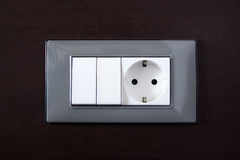 Wooden wall with power outlet and light switch Stock Image