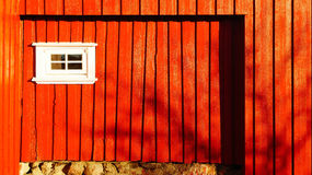 Wooden wall of a traditional building. With red boards, a small white window wood. Telemark region of Norway Royalty Free Stock Image