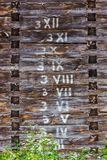 Wooden wall with written arabic and roman numbers in logs in ord. Er stock photo
