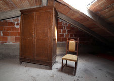 Wooden wardrobe and an antique chair in the dusty attic Royalty Free Stock Images