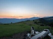 Wooden warertrough on mountain pasture. Carpathians mountains, west Ukraine. Ukrainian nature background. Evening sky. Illuminated by the sun. Hillsides covered stock photos
