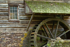 Wooden water paddle wheel and mossy stones on the side of a old. Grist mill in autumn with ferns stock photo