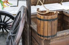 Wooden water well with a bucket tied on a rope stock images