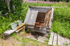 Wooden water well with the open door and a buckets. Village wooden water well with the open door and a buckets of water in the summer sunny day Royalty Free Stock Images