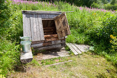 Wooden water well with the open door and a buckets. Village wooden water well with the open door and a buckets of water in the summer sunny day Royalty Free Stock Photography