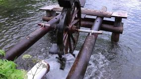 Wooden water wheel turning under power, water mill on a Lake. Summer stock footage