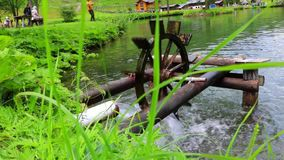 Wooden water wheel turning under power, water mill on a Lake. Summer stock video
