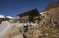 The wooden watermill beside the road with views of the snow-capped mountains. Austrian Alps Stock Images