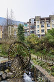 Wooden waterwheel before mountainside dwelling buildings Stock Photography