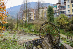Wooden waterwheel before riverside houses at mountain foot Stock Photos