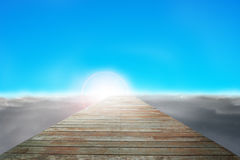 Wooden way direct to sun with cloudy below and blue sky. Wooden way direct to sun with cloudy below and clear blue sky stock photo